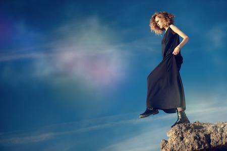 Una bella ragazza è in posa fuori in un abito nero sulla cima di una roccia. Concetto di moda. Archivio Fotografico