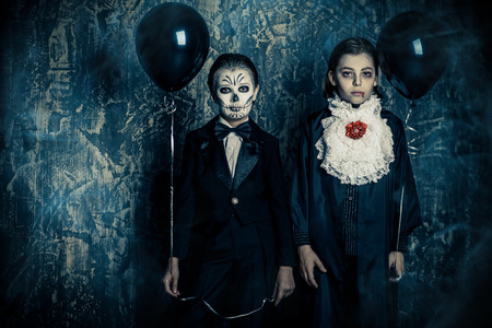 Children in halloween carnival costumes stand by a grunge wall with black balloons. Happy Halloween! Фото со стока