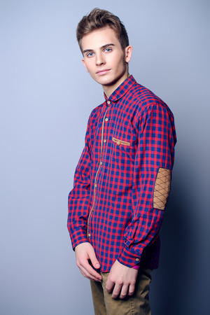 Portrait of a handsome teenage boy in a plaid shirt over gray background. Studio shot. Teen fashion.