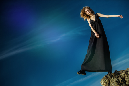 A beautiful young girl is posing outside in a black dress on the top of a rock. Fashion concept.