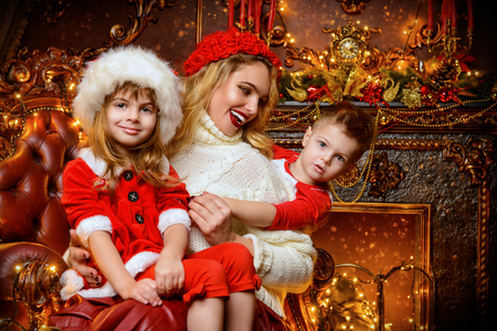 Mom with children sitting on a chair on the background of Christmas decorations. Time for miracles.