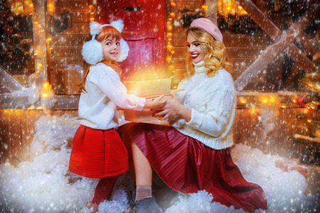 Happy mother and daughter open a gift near the house, decorated for Christmas. Merry Christmas and Happy New Year.