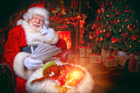 Santa Claus is at his home reading letters with wishes from children. Merry Christmas and Happy New Year. Miracle time. Stock Photo