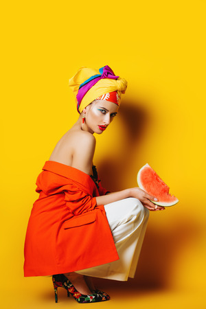 Portrait of a fashionable woman with watermelon and bright make-up. Yellow background. Beauty, fashion, make-up concept. Foto de archivo