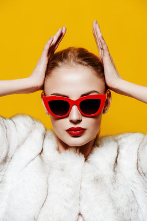 Gorgeous blonde woman posing in luxurious fur coat and pin-up sunglasses. Yellow background. Fashion, beauty. Studio shot. Archivio Fotografico