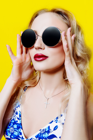 Dreamy summer girl. Beautiful young woman in sunglasses over bright yellow background.