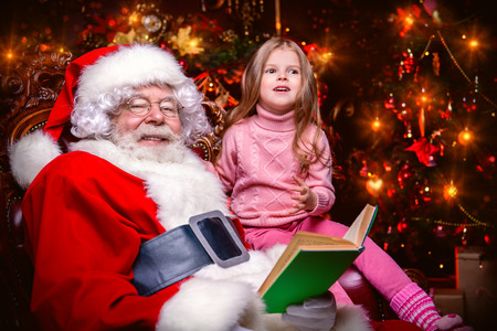 A happy young girl is sitting with Santa Claus at home. Merry Christmas and Happy New Year. Miracle time.
