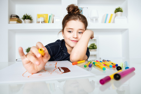 A portrait of a pretty cute girl sitting at a table and drawing a picture. Beauty, creativity, kids. Banque d'images
