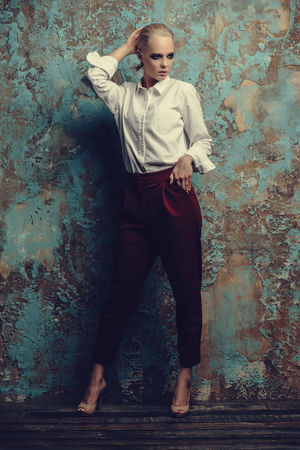 Fashion shot. Attractive young model posing in a white shirt and red trousers. Man's style clothing. White background. Archivio Fotografico - 111588874