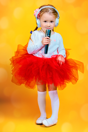 A portrait of a bright young pretty girl in skirt with a microphone. Fashion for kids. Фото со стока
