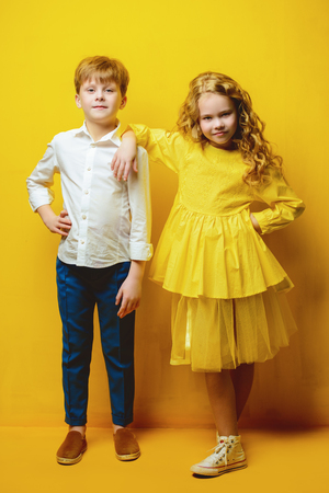 Childrens fashion. Beautiful boy and girl in elegant clothes posing together at studio over yellow background. Full length portrait.
