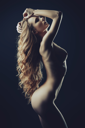 Nude girl posing on a black background. Female nude silhouette. Young sexy woman with long curly hair. Archivio Fotografico - 111518636