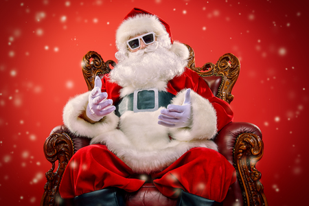 Cool modern Santa Claus in sunglasses sitting in his armchair over red background. Christmas concept.