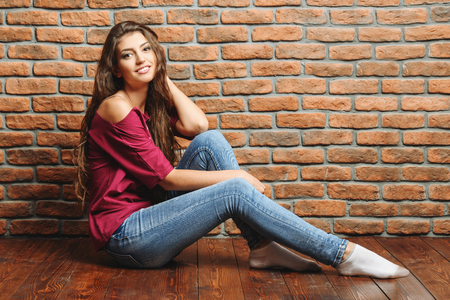 An attractive lady over a brick wall. Portrait. Natural beauty.