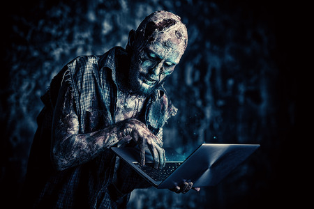 Creepy scary zombie is with a laptop. Halloween. Horror film.