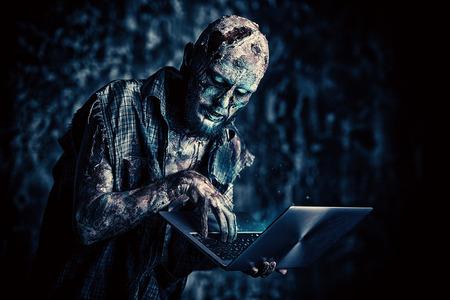 El zombi aterrador espeluznante está con una computadora portátil. Víspera de Todos los Santos. Película de terror. Foto de archivo
