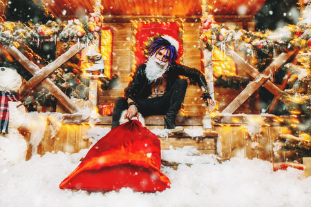 Ð¡heerful punk Santa fools around near his house with a bag of gifts in his hands.