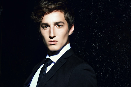 Portrait of a handsome young man posing in black suit and white shirt over black background. Male beauty, fashion. Hair styling. Stock Photo