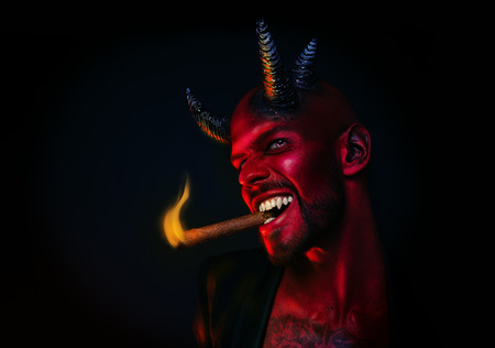 A close-up portrait of a bad demon with a cigar. Horror movie, nightmare. Halloween. Stock Photo