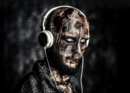 Creepy scary zombie is listening to music with headphones. Halloween. Horror film. Archivio Fotografico