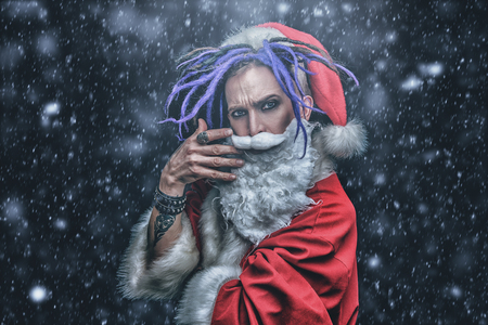 Portrait of a cool punk Santa Claus with bright dreadlocks over black background. Standard-Bild