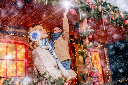 Mother and her son are on the porch of their house decorated for Christmas. Family miracle time. Merry Christmas and Happy New Year. Stock Photo