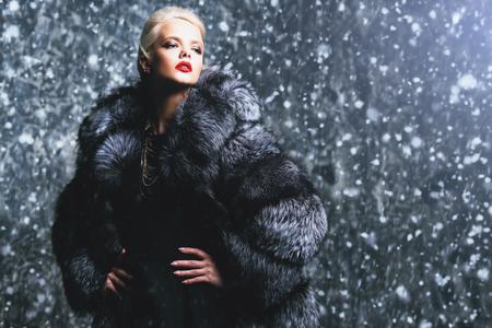 Gorgeous blonde woman posing in luxurious fur coat.
