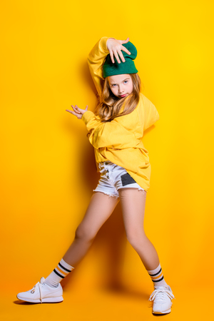 A full length shot of a bright emotional girl. Fashion for active kids.