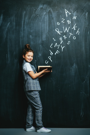 A full length portrait of a cute girl standing with a book over a blackboard.