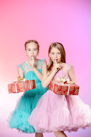 Two pretty little girls dressed in beautiful festive dresses  with gift boxes in their hands. Kids fashion concept.