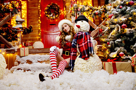 Sexy Santa girl in red body suit and striped stockings poses next to a snowman near the house of Santa, decorated with festive lights. Christmas and New Year concept.