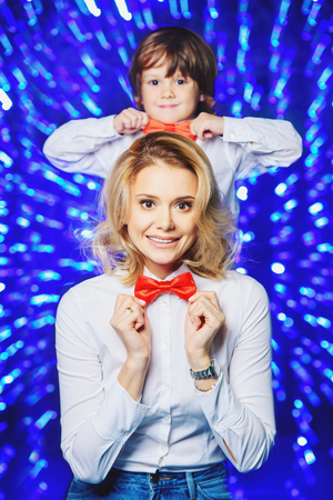 Portrait of a happy mom with her little son wearing white shirts and bow ties. Merry Christmas and Happy New Year.