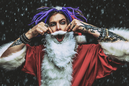 Portrait of a cool punk Santa Claus with bright dreadlocks over black background. 스톡 콘텐츠 - 112476633
