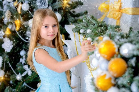 Pretty nine year old girl stands in a beautiful room near a Christmas tree and a fireplace. Luxurious apartments decorated for Christmas. Merry Christmas and Happy New Year.