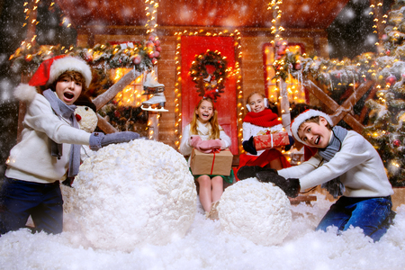 Happy children make a snowman near the house decorated for Christmas. Merry Christmas and Happy New Year. Winter holidays concept. 免版税图像