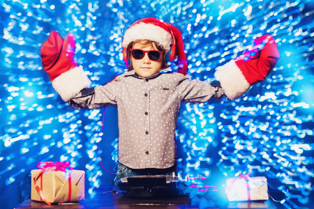 A young dj playing music in sunglasses. Merry Christmas and Happy New Year. 免版税图像