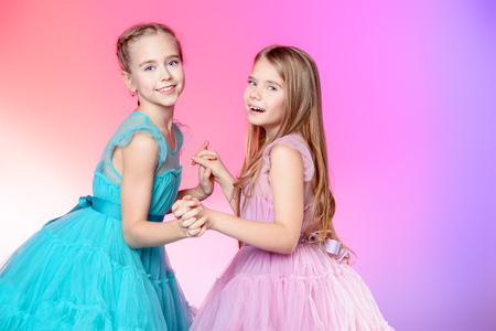 Two pretty little girls dressed in beautiful festive dresses. Kids fashion concept.