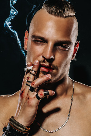 Portrait of a brutal handsome man with naked torso, who smokes a cigarette. Male beauty, health. Rocker, punk. Stok Fotoğraf