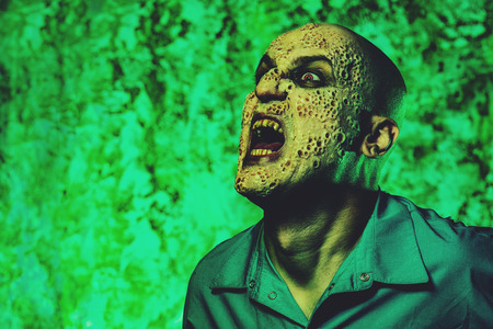 A portrait of a sick screaming man in the green light. Desparation, hopelessness. Stockfoto