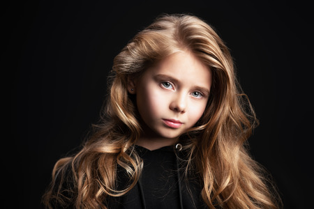 A close-up portrait of a cute emotional girl posing over the black background in studio. Beauty, fashion for kids and teenagers. Foto de archivo