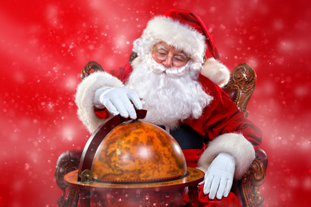 Christmas, tourist trip concept. Santa Claus sitting on his armchair and making plans of travelling around the planet. Christmas time. Time for miracles. Copy space. Stock Photo