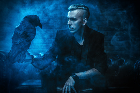 A vampire man is sitting on the sofa and holding a black raven. Halloween night. Beauty, fashion.
