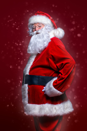 Christmas concept. Portrait of a fairytale Santa Claus over red background. Good old traditions. Family holidays. 写真素材