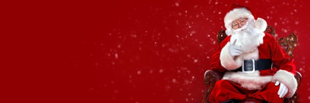 Christmas and New Year concept. Portrait of good old Santa Claus sitting in his armchair. Red background. Stock Photo
