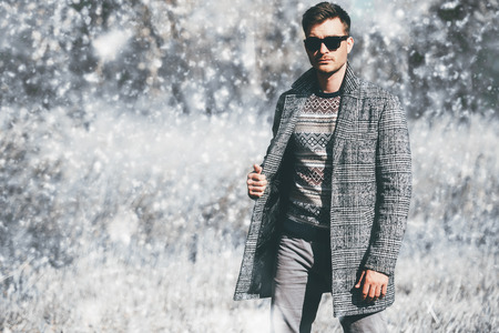 A handsome man in countryside. Winter fashion for men. Freedom, lifestyle. Standard-Bild