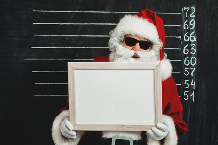 A portrait of Santa Claus in sunglasses holding a plate.