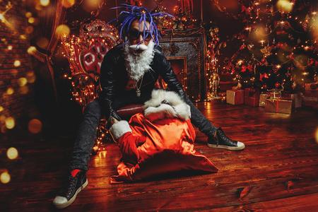 Ð¡heerful punk Santa with a bag of gifts in his hands  in luxurious apartments decorated for Christmas. Stock Photo