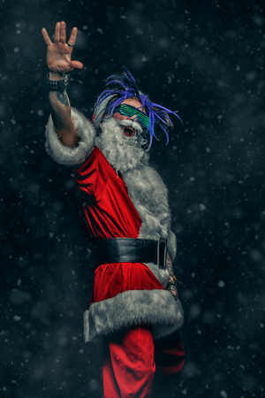 Portrait of a cool punk Santa Claus with bright dreadlocks over black background. 写真素材