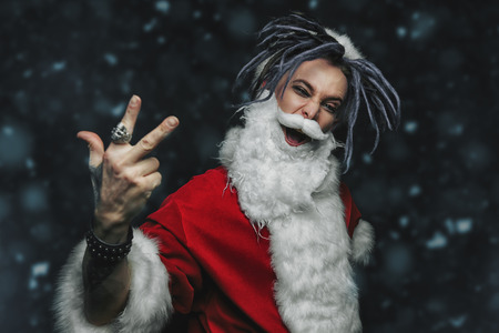 Portrait of a cool punk Santa Claus with bright dreadlocks at the snowy weather. 스톡 콘텐츠 - 112416567