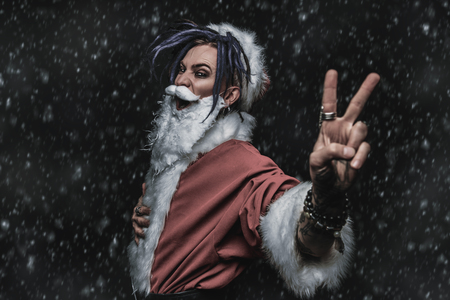 Portrait of a cool punk Santa Claus with bright dreadlocks over black background. Stock Photo